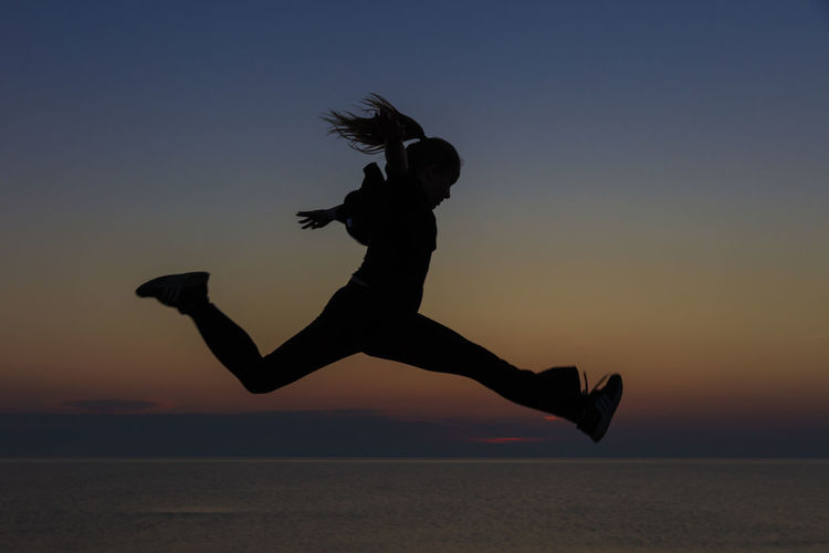 Silhouette Girl Jumping At Beach Against Sky