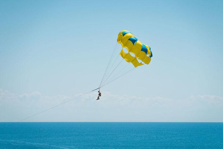 Parasailing over sea against sky