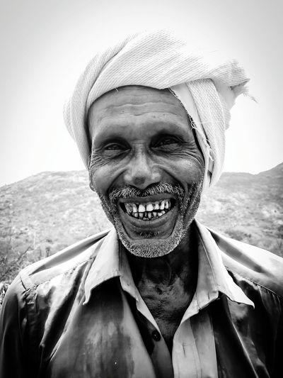 Portrait of cheerful mature man wearing headscarf