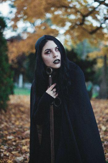 tastes like cyanide Witch Dark Photography Dark Cloak Sword Graveyard Cemetery Warm Clothing Young Women Beautiful Woman Tree Leaf Looking At Camera
