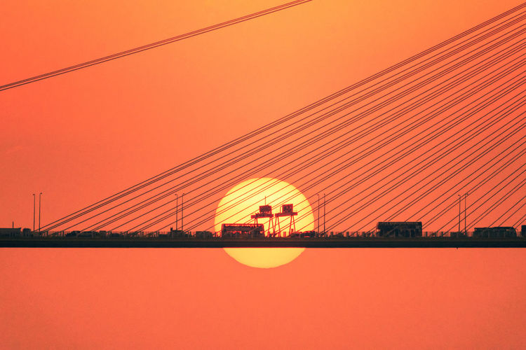 Vehicles On Bridge During Sunset