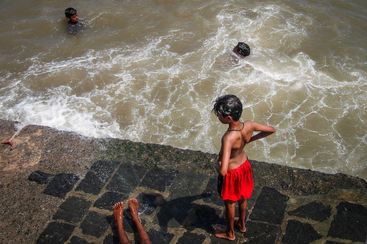 Fun at the harbor Fun India Beach Child Childhood Clothing Day Full Length High Angle View Leisure Activity Lifestyles Motion Nature Outdoors People Rear View Sea Shirtless Shorts Standing Water Waterfront Wave