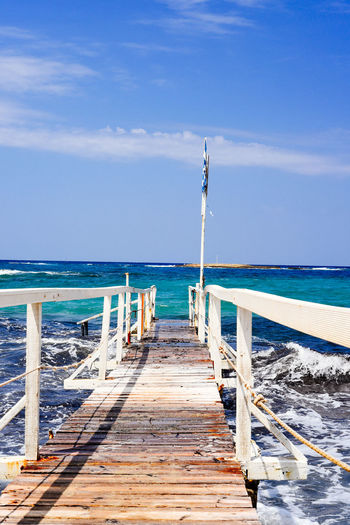 Jetty leading to sea against clear sky