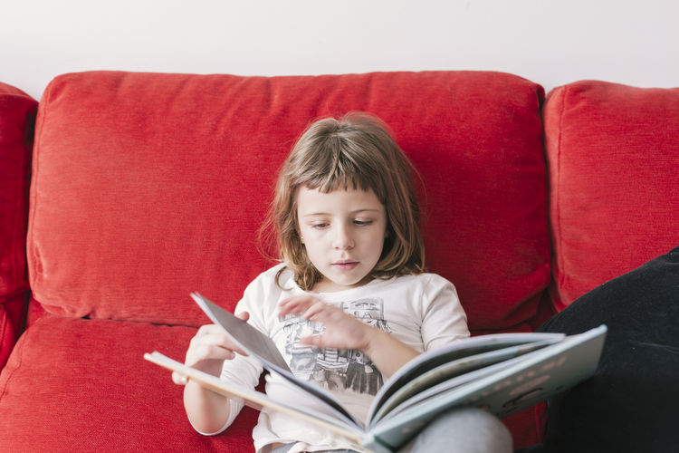 Girl looking away while sitting on sofa