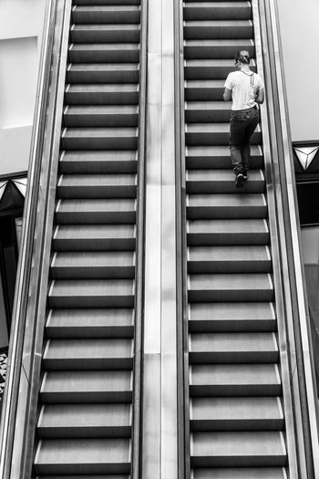 Woman Walking On Escalator