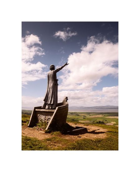 Digital composite image of statue on field against sky