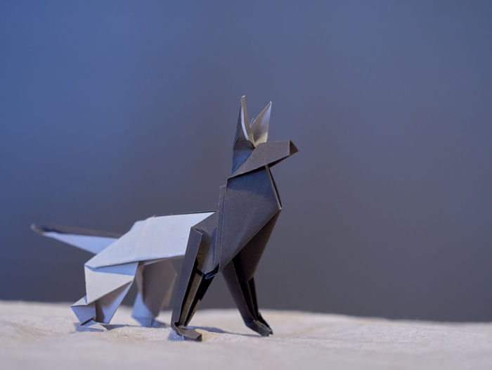 Gray irigami dog on chair against blue background