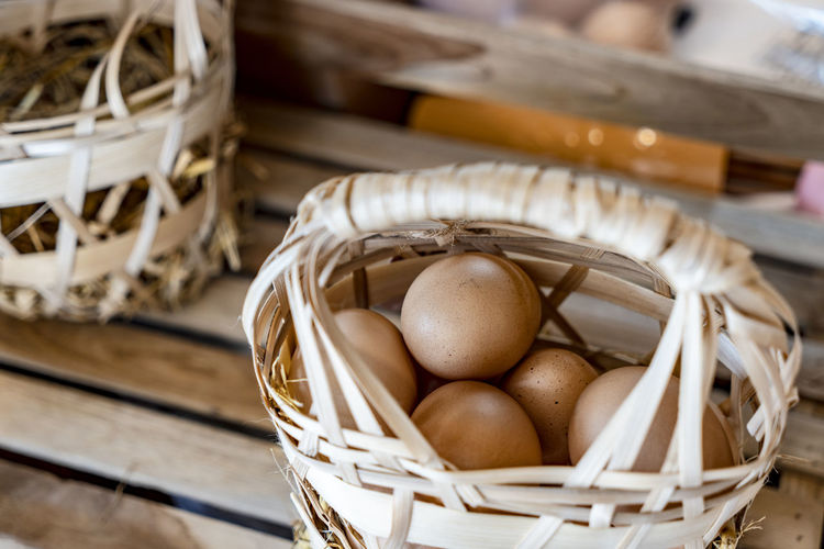 organic fresh eggs for sell ready to carry in bamboo basket handle Container Basket Wellbeing Egg Healthy Eating Selective Focus Indoors  Close-up Still Life No People Wood - Material Wicker Raw Food Food Food And Drink Freshness High Angle View Table Brown Focus On Foreground
