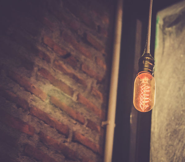 Low Angle View Of Illuminated Light Bulb Hanging By Brick Wall