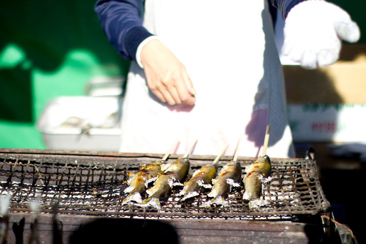 Midsection of chef standing by fish on barbecue grill