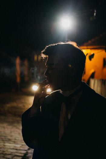 Young Man smoking a cigarette Bad Habit Cigarette  Focus On Foreground Headshot Holding Illuminated Leisure Activity Lens Flare Lifestyles Night One Person Portrait Real People Smoking - Activity Smoking Issues Social Issues Young Adult Young Men