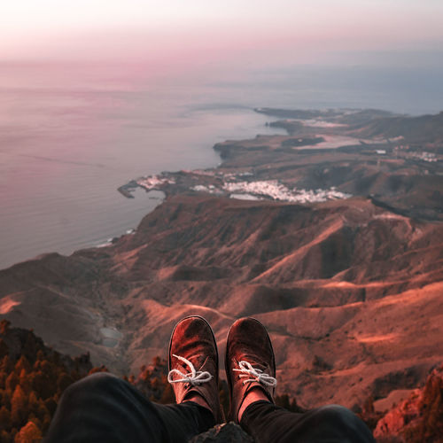 Low section of man sitting on cliff against sea during sunset