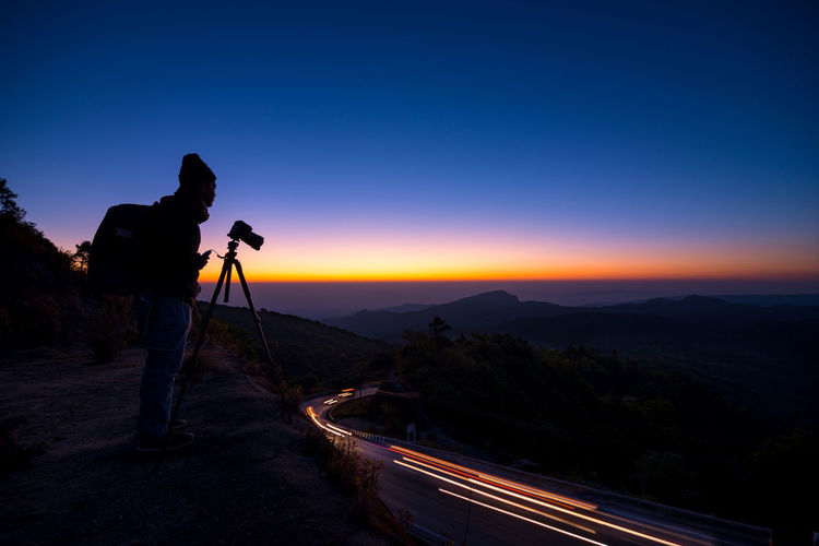 Side View Of Man With Camera And Tripod Standing On Mountain Against Sky During Sunset
