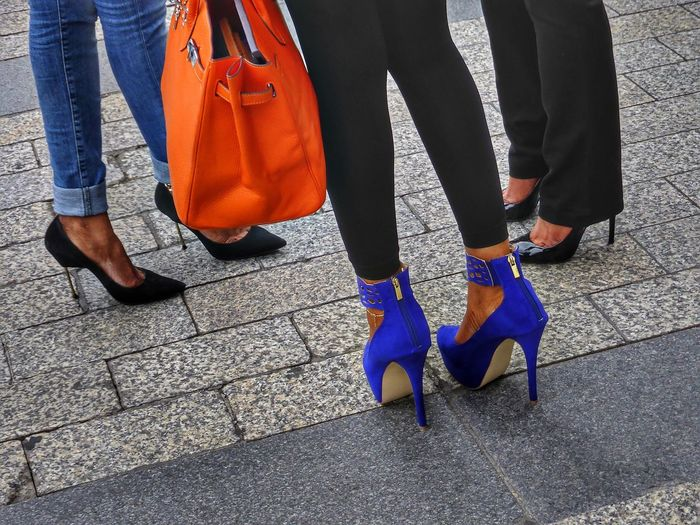 Street photography of lower section of Women with black and purple high heels and orange handbag Handbag  High Heels Fashion Low Section Real People Human Leg Human Body Part City Body Part Shoe Street Day Footpath Lifestyles Women Walking Bag Group Of People Standing Paving Stone
