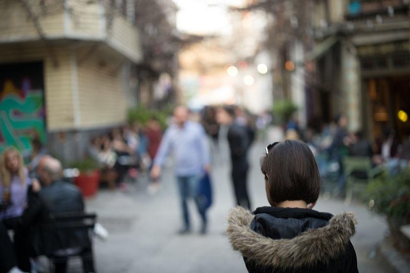 Rear view of woman walking against people on footpath