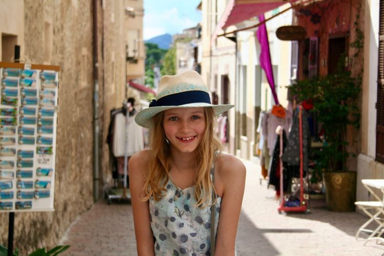 Portrait of smiling girl wearing hat in town