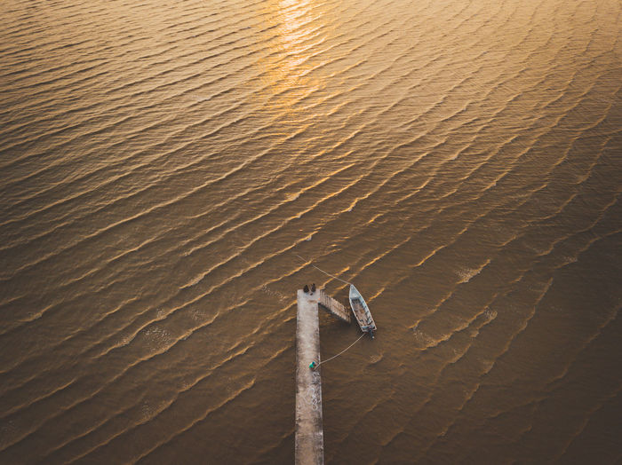 High angle view of fishing boat moored at sea during sunset