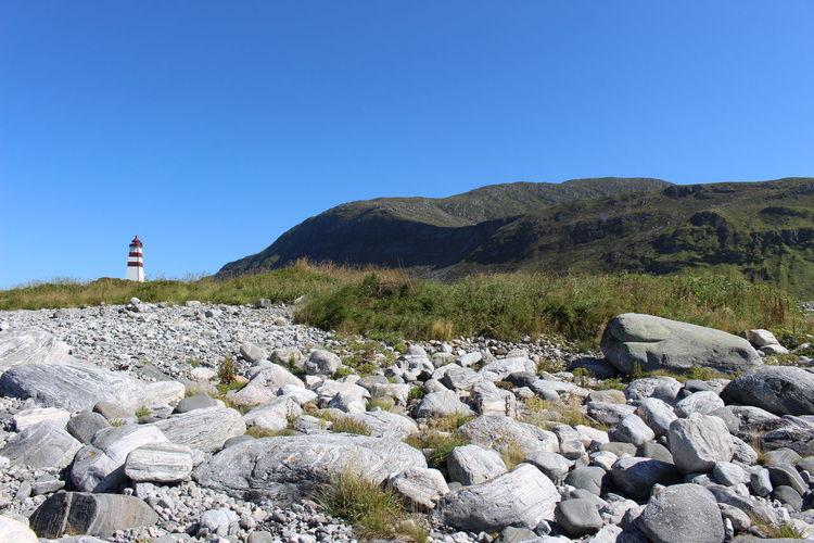 Rocks on land against clear blue sky