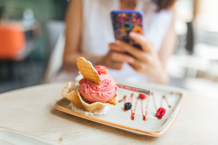 Midsection of person holding ice cream cone on table