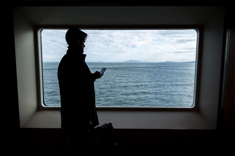 Man using phone against window at sea