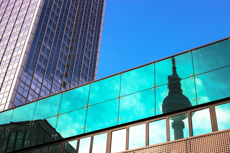 Low angle view of glass building against blue sky
