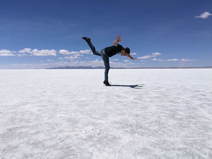 Full length of man balancing at salar de uyuni against blue sky on sunny day