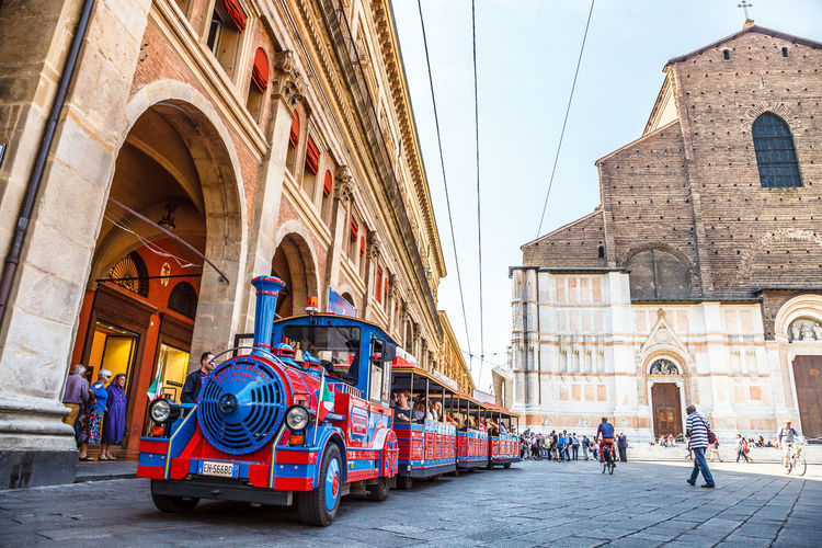 Bologna, Italy - May 28, 2016: Palazzo Re Enzo, historical landmark palace and heart of economic and social activities of the city with many people and the main square called Piazza Maggiore. People walking in via Rizzoli, restricted traffic zone, closed to traffic during the day on Saturday. The Two Towers, icons of Bologna, on background. Tourist train at side of Palazzo dei Banchi in Piazza Maggiore. San Luca Espress is the tourist line which connects the historic center with the Basilica of San Luca. Bologna Bologna, Italy Cathedral Church City Piazza Maggiore San Luca Tourist Arch Architecture Asinelli Asinelli Tower  Building Building Exterior Built Structure City Crowd Day Group Of People History Incidental People Italian Italy Outdoors People Place Of Worship Real People Religion San Petronio Street Streetphotography The Past Tourism Town Train Transportation Travel Travel Destinations Women