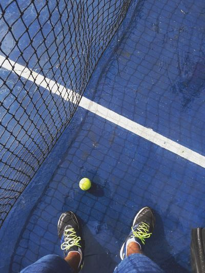 Low Section Of Man Standing By Net And Ball On Blue Tennis Court