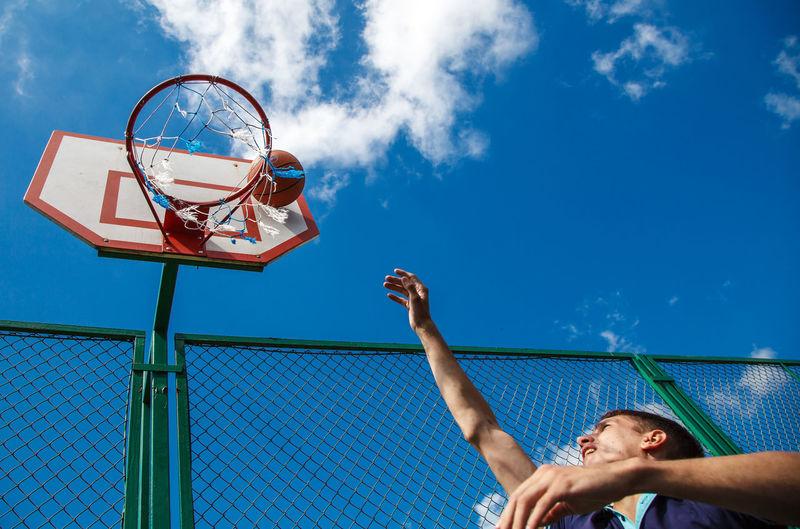Low angle view of man playing basketball sky