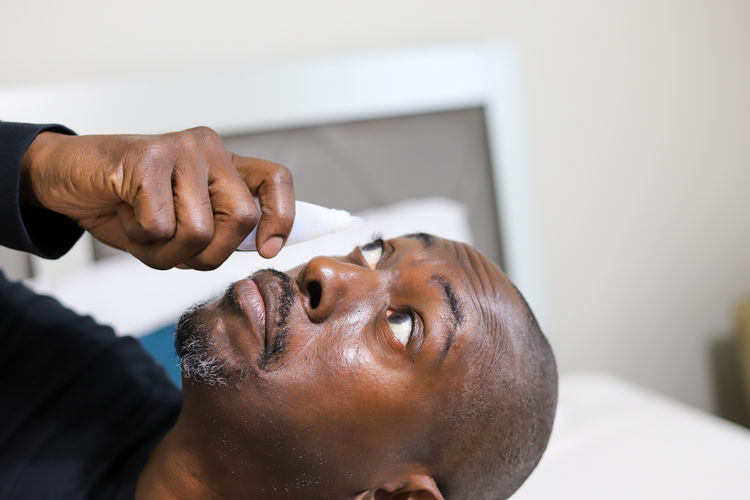 A portrait of an african-american man putting eye drops in his eye