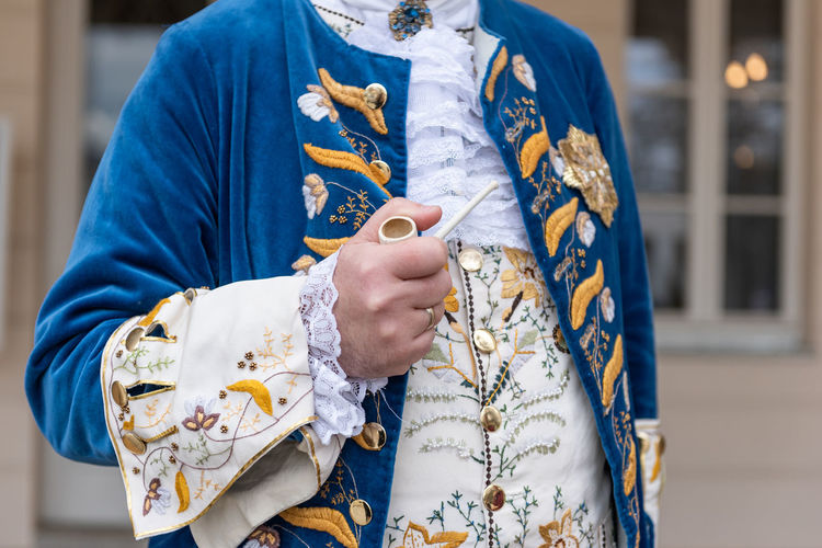 The details of man dressed in a baroque costume. a hand holding a pipe, golden buttons, vest.
