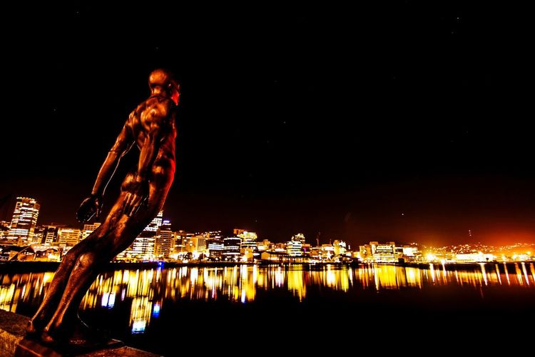 """""""Solace to the Wind"""" sculpture looks out over the Wellington waterfront on a perfect calm evening. Night Illuminated Reflection Water Built Structure Architecture Building Exterior Sky Clear Sky Waterfront Dark Looking Scenics Harbor Tranquil Scene Sculpture"""