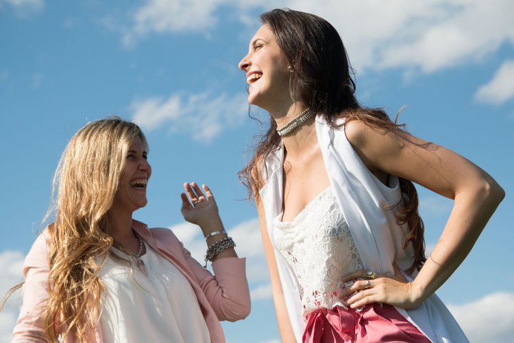 Low angle view of young women laughing while looking away against sky