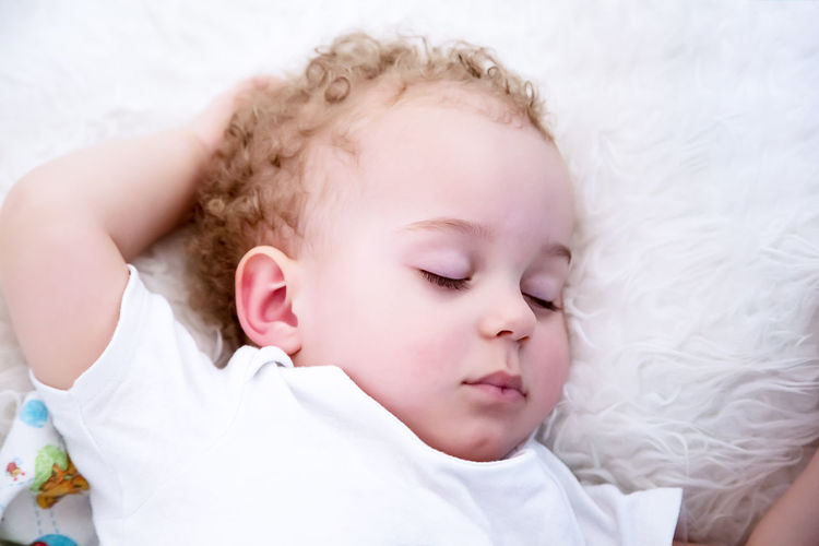 Close-up of baby boy sleeping on bed