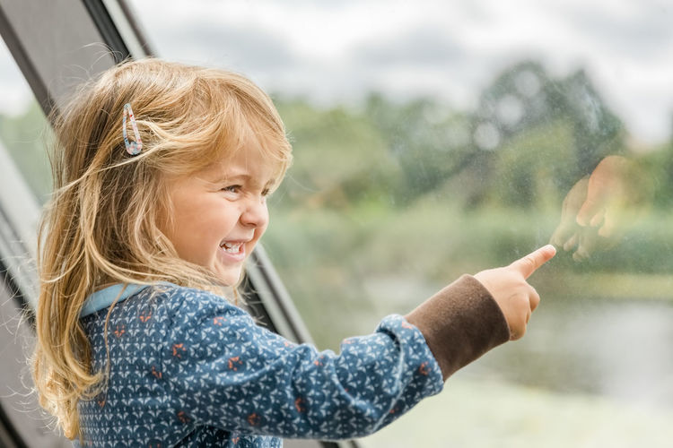 Cute smiling girl pointing on window