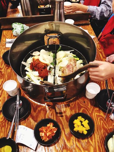 Chicken Galbi cooking on a hot plate on a table in a restaurant in Seoul in South Korea. Dinner Lunch Eating Out Restaurant Delicious Taste Gourmet Cuisine South Korea Chicken Galbi Food And Drink Food Freshness Ready-to-eat Human Hand Hand Human Body Part Indoors  High Angle View Table Meal People Healthy Eating Plate