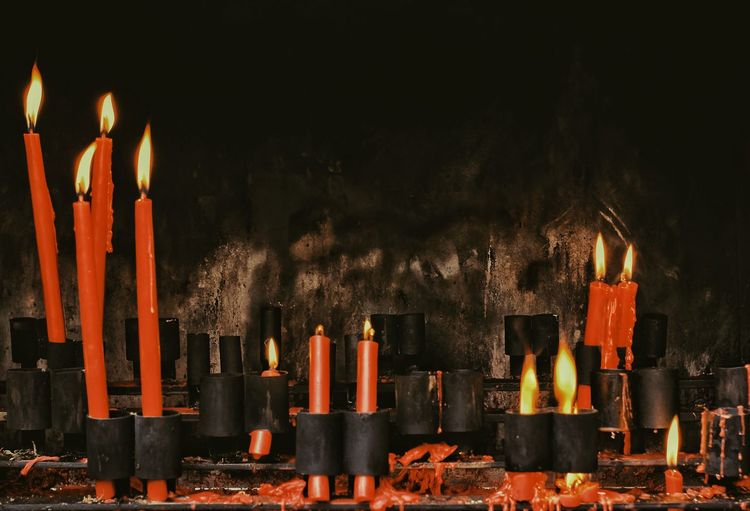 Illuminated candles in temple against wall