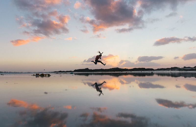 Woman Jumping Over Lakeshore Against Sky During Sunset