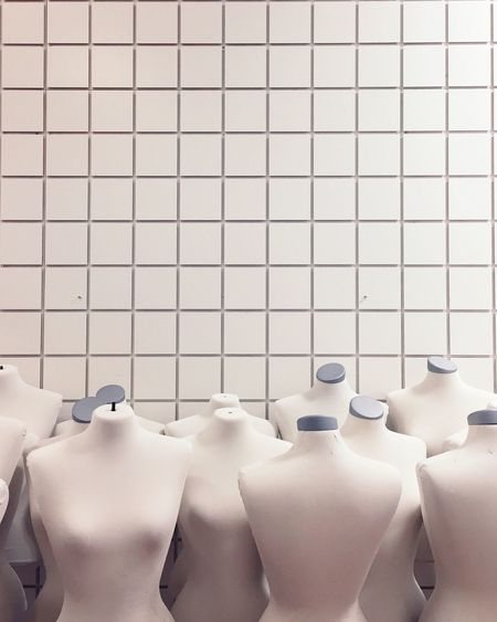 Female Mannequins Against Tile Wall