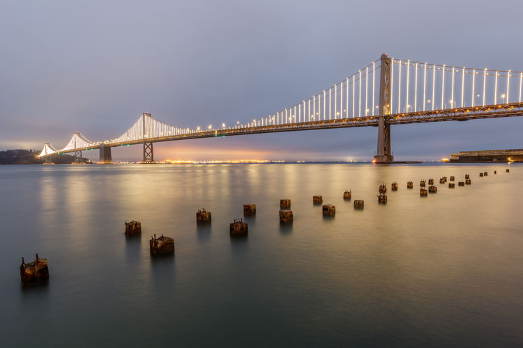 Panoramic view of the Bay Bridge from the Port of San Francisco. The Embarcadero, San Francisco, California, USA. Architecture Port Sightseeing Toll Bridge Road Bridge Concrete Bridge Steel Bridge Interstate 80 Overcast Fog Motion Blur Outdoors Scenics Scenery Piling Engineering Structure Modern Panoramic Tourism Tourist Attraction Travel Destinations California Bay Bay Area Bridge Suspension Bridge Transportation Pier Ruins Clouds Embarcadero San Francisco Backgrounds Night Urban Landmark Reflection Skyline View City Cityscape Light Evening Building Landscape Sky Water