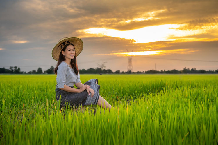 Side view of thoughtful woman sitting on land against sky during sunset