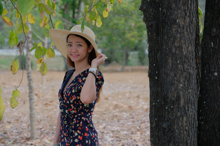 Portrait of woman standing against tree trunk
