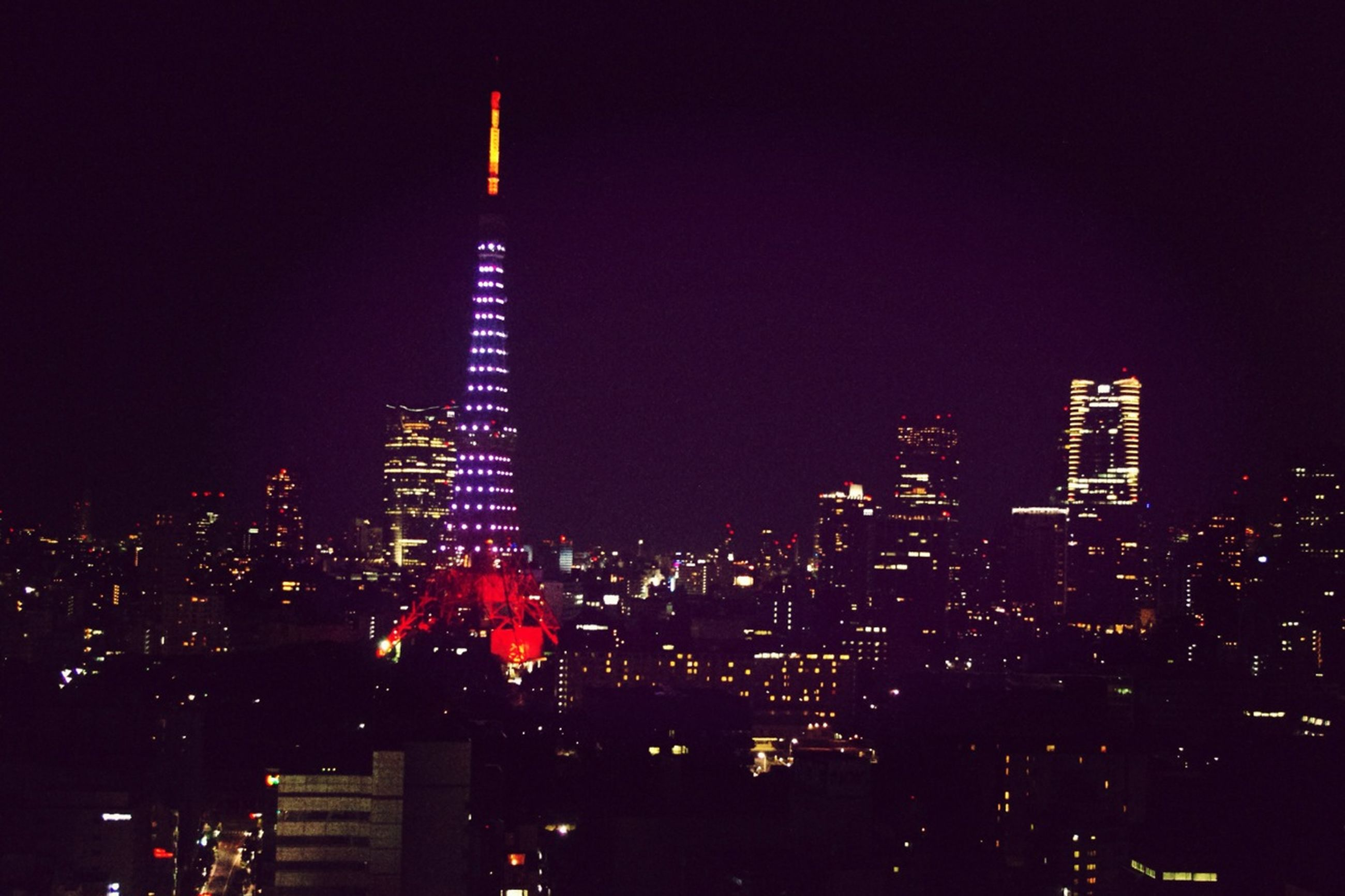 building exterior, illuminated, night, city, skyscraper, architecture, built structure, tall - high, tower, cityscape, modern, office building, clear sky, capital cities, urban skyline, financial district, tall, city life, crowded, travel destinations