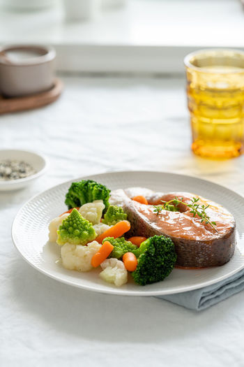 Steam salmon and vegetables, paleo, keto, fodmap, dash diet. side view, vertical. mediterranean diet