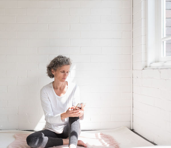 Young woman sitting against wall