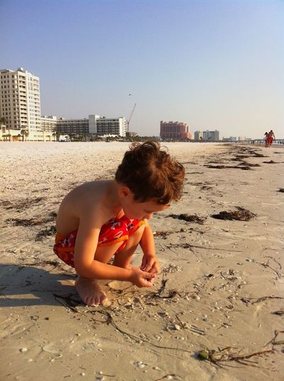 Shirtless boy playing at beach against clear sky