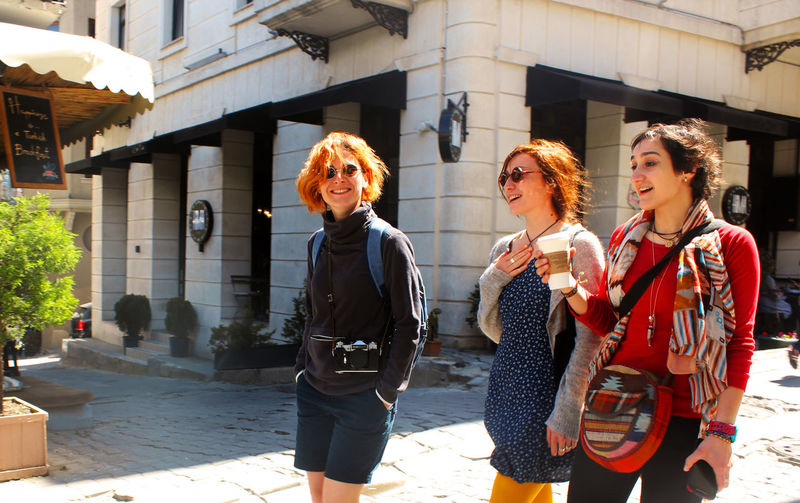 Young women walking with coffee cup at sunlight day in the street of istanbul, turkey. happy faces