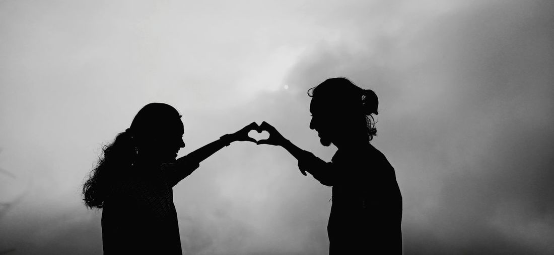 Silhouette couple making heart shape standing against sky