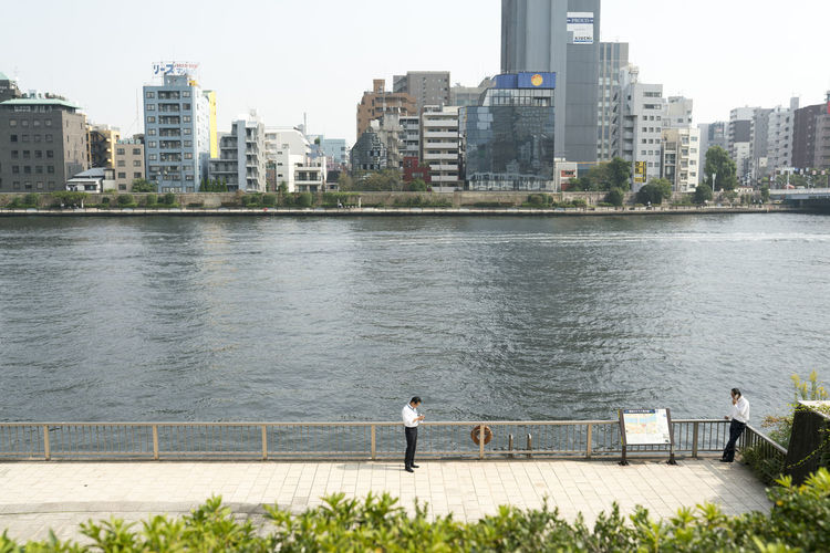Rear view of men standing on railing by river against buildings