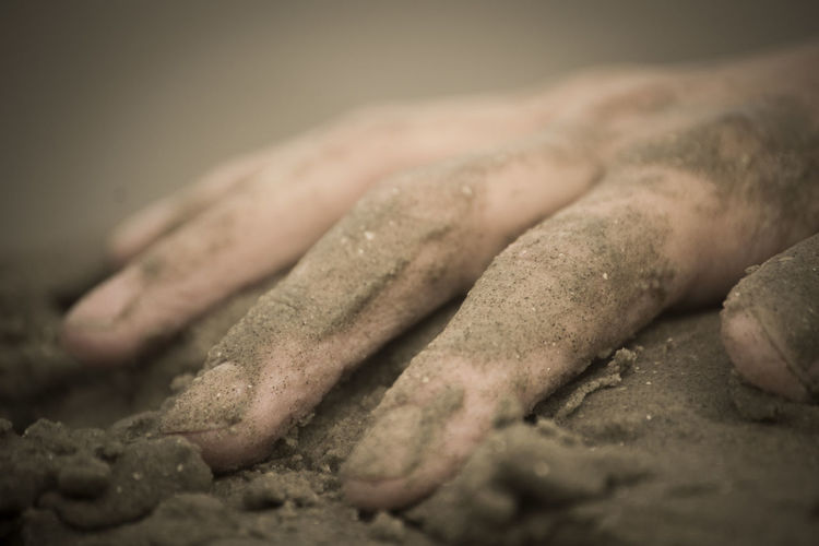 Close-up of hands on sand